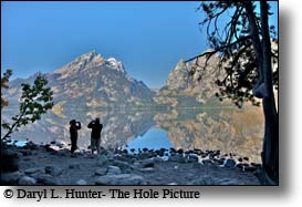 Couple enjoying the view of the Grand Tetons reflectin their glory into the water of Jenny Lake