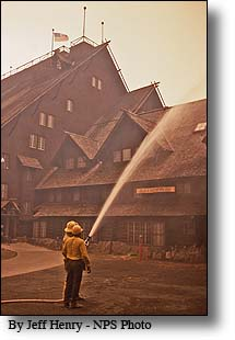 firefighter keeping water on Old faithful Lodge in an effort to keep it from burning